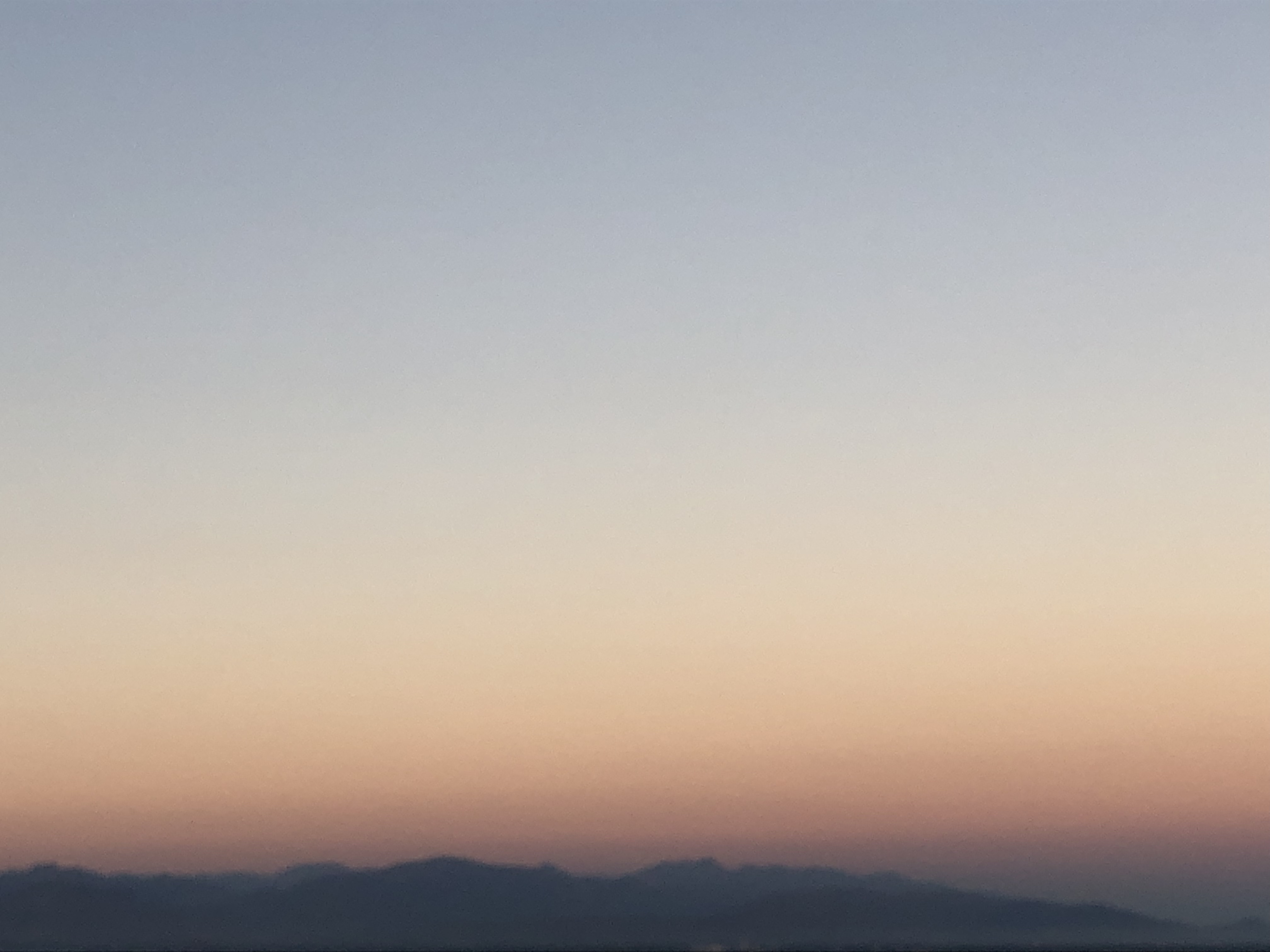 hazy sky with mountains in the distance